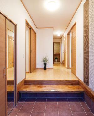 磨き上げられた式台が美しい玄関ホール。右手の壁には、防臭・調湿効果のあるデザインスタイル・エコカラットを使用。左手には大容量のシューズクロークを備えている。