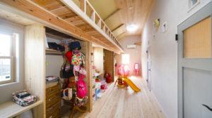 ブルーグレーの室内ドアの向こうには子供たちのワンダーランドが広がっている。造作のデスクと収納は使い勝手がよさそう。