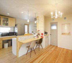 壁面の収納棚とカウンターキッチンは「ウッドワン」でそろえ、ガラスのペンダントライトなどでナチュラルな雰囲気に。