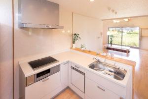L字型の対面キッチンは、少ない移動で使えるのも魅力。リビングを介して庭が見える開放感もうれしいポイント。