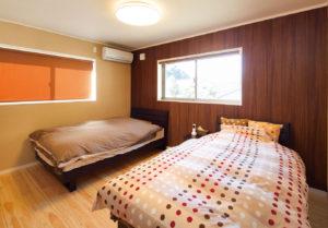 ベージュ×ダークブラウンのシックな寝室。壁を一面のみ高級感のあるウッド調に仕上げている。大容量ウォークインクローゼットも備えた。