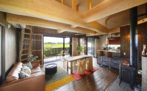 キッチンは対面式。薪ストーブが置かれたフラットな土間は玄関兼用。薪運びなど土足で作業できるのもポイント。