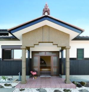 玄関ポーチの屋根には厄除け・魔除けの意味を持つ、鬼面の鬼瓦を。アプローチや庭は、ご主人が少しずつ手を入れて仕上げている。