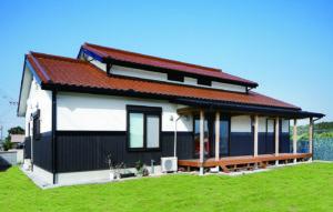 ゆったりと広がる芝庭や南国の青空に映えるT低。焼きスギの外壁や破風板、樋の黒が効いた、個性あるれる美しいデザイン。